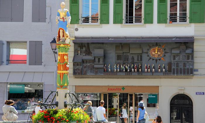 Фонтан Правосудия на фоне экстравагантных часов Лозанны